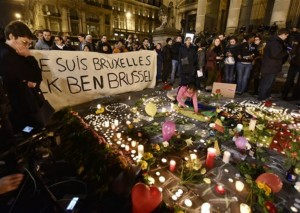"""People holding a banner reading """"I am Brussels"""" behind flowers and candles to mourn for the victims at Place de la Bourse in the center of Brussels, Tuesday, March 22, 2016. Bombs exploded at the Brussels airport and one of the city's metro stations Tuesday, killing and wounding scores of people, as a European capital was again locked down amid heightened security threats, Brussels, Belgium, March 22, 2016 