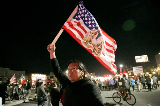 A protester holds a U.S. flag as hundreds gather in downtown Salt Lake City, where Republican presidential candidate Donald Trump held a campaign rally, Friday. Salt Lake City, Utah, March 18, 2016   Photo by Benjamin Zack/Standard-Examiner via AP; St. George News