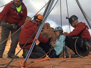 Brittany Fisher sits under the vortex as Washington County Sheriff's high angle rope rescue team members Mike Thomas, Jerod Hummel and Rob Girouard get her ready to rappel Cougar Cliffs. Fisher suffered serious injuries when she fell from the rocks while there on a rappelling excursion March 12, 2012. Four years later she returned to rappel the cliffs again. Cougar Cliffs area of Washington County, Utah, March 12, 2016 | Photo by Rick Graf, St. George News