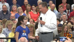"""L-R: A 13-year-old girl takes the hand of Republican presidential candidate John Kasich and asks him, """"What's the first thing you would change if you become president?"""" Kasich replied, """"The way that people get along with one another."""" Kasich was at a town hall meeting at the Dixie Center St. George, St. George, Utah, March 19, 2016 