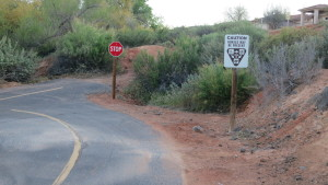 A sign with yield guidelines and a stop sign for trail users on the Snow Canyon Trail near Bluff Street, April 11, 2016. Multi-use trails along major roads often cross driveways or side streets, and thus have stop signs. Riding on the road allows cyclists to ride through and in a way that is more predictable for motorists. St. George, Utah, April 13, 2016 | Photo by Tim Tabor, St. George News