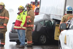 Emergency responders tended to an accident scene on southbound Interstate 15 Saturday. A woman driving a Toyota Prius lost control, hitting the center divider and then careening back into traffic, where the car embedded itself under a semitrailer. Washington County, Utah, April 9, 2016 | Photo by Ric Wayman, St. George News