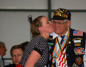 World War II, Korean and Vietnam War veteran, Al Arruda gets a kiss on the cheek from a Red Rock Swing Hottie at the 1940s Hangar Dance. St. George, Utah, May 20, 2016 | Photo by Hollie Reina, St. George News