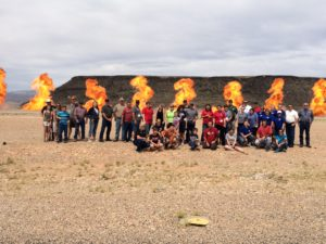 Participants of a mass casualty drill organized by the Utah Association of Emergency Technicians line up for a group photo while fireballs explode behind them. St. George, Utah, May 20, 2016 | Photo by Don Gilman, St. George News