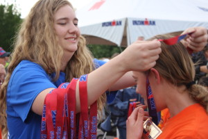 A volunteer presents a medal to a young competitor at the Ironman Kids Fun Run in St. George, Utah, May 6, 2016 | Photo by Don Gilman, St. George News