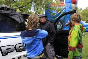 """Cedar City Police Sgt. Jerry Womack talks with kids about the job of a police officer and explains the various pieces of equipment in their cars Saturday.""""Public Safety Responder Appreciation Day,"""" created to recognize and thank first responders. Main Street Park, Cedar City, Utah, May 6, 2016 