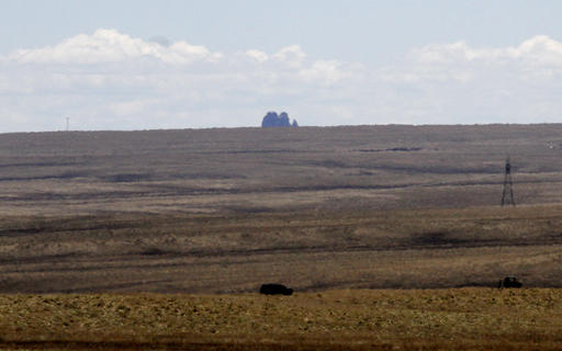 Two vehicles are seen in the distance near the area where Ashlynne Mike's body was discovered, in south of Shiprock, N.M., on Tuesday, May 3, 2016. Police gleaned some information about the suspect from the younger brother of Ashlynne, whose body was found Tuesday near the distinct rock formation that the rural town of Shiprock, is named for. Authorities are poring over parts of the Navajo Nation in search of the man who snatched the children and killed Ashlynne. | Photo by Jon Austria/The Daily Times via AP; St. George News