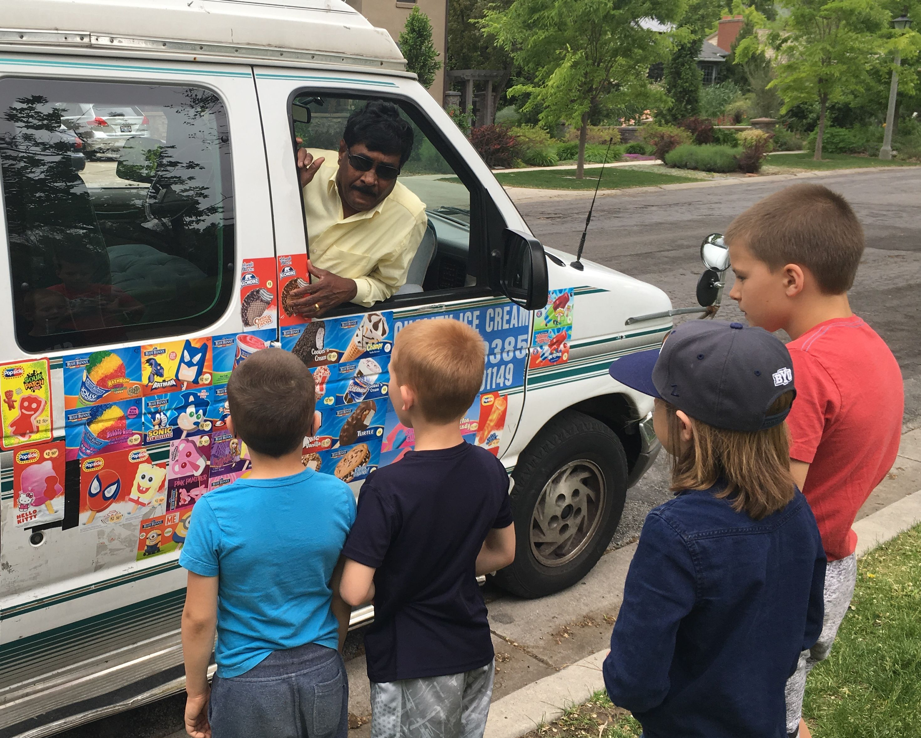 Four neighborhood boys reviewing treat options at the ice cream van, Salt Lake City, Utah, May 2016. | Photo by Kat Dayton, St. George News