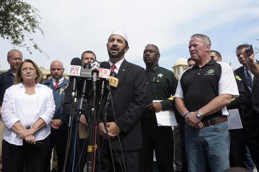 Imam Muhammad Musri, center, president of the Islamic Society of Central Florida, addresses reporters while flanked by members of law enforcement and community leaders during a news conference after a shooting involving multiple fatalities at a nightclub Sunday in Orlando, Florida, June 12, 2016 | AP Photo/Phelan M. Ebenhack; St. George News
