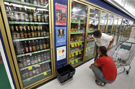 In this June 9, 2016 photo, customers shop for beer at Liquor Mart in Boulder, Colo. On June 10, Colorado's governor signed a bill to gradually allow grocery stores to sell full-strength beer, liquor and wine, the biggest change to state liquor laws since the end of Prohibition. The bill signed Friday by Gov. John Hickenlooper starts a 20-year phase-in for grocers to acquire liquor licenses, sometimes by paying for those held by neighboring liquor stores. (AP Photo/Brennan Linsley)