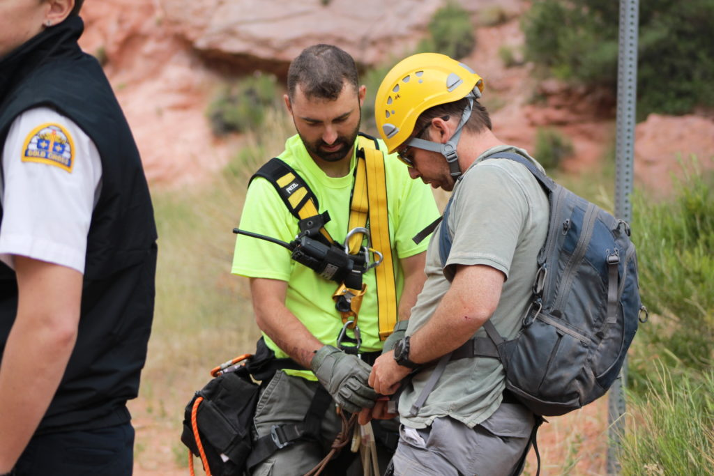 Iron County Sheriff's Ropes Team member helps rescued hiker remove his safety harness after he was rescued from 600-foot cliff in Cedar City Saturday, Cedar City, Utah, June 11, 2016 | Photo by Tracie Sullivan, St. George/Cedar City News