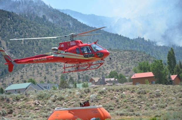 Type 3 (light) helicopter dipping for water to suppress a lightning-caused fire burning on Saddle Mountain in the Pine Valley Wilderness of the Dixie National Forest, Washington County, Utah, June 28, 2016 | Photo courtesy of InciWeb, St. George News