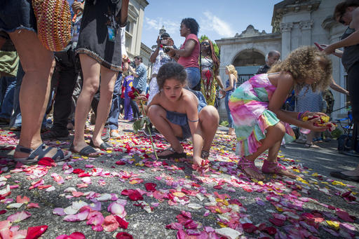 Children and spectators collect flowers from the road that Muhammad Ali's funeral procession passed along to enter Cave Hill Cemetery, Friday in Louisville, Kentucky, June 10, 2016 | AP Photo/John Minchillo; St. George News