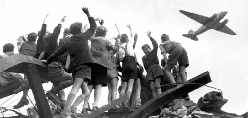 """Touched by the hunger-stricken condition of children during almost nonstop flying during the Berlin Airlift following WWII, Gail Halvorsen """"candy bomb"""" the children with gum and Hershey bars. West Berlin, Germany, circa 1948 