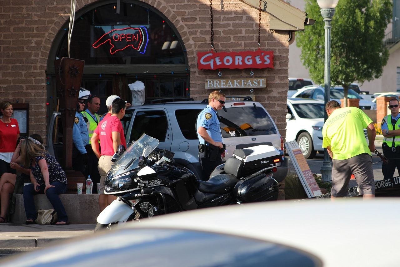 Officers and emergency responders tend to a three-car collision that sent a Ford Escape into the entrance of George's Corner Restaurant located at 2 W. St. George Blvd, St. George, Utah, June 29, 2016 | Photo by Cody Blowers, St. George News