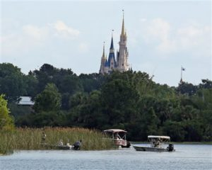 In the shadow of the Magic Kingdom Florida Fish and Wildlife Conservation Officers search for the body of a young boy Wednesday after the boy was snatched off the shore and dragged underwater by an alligator Tuesday night at Grand Floridian Resort at Disney World, Lake Buena Vista, Florida, June 15, 2016 | Photo by Red Huber/Orlando Sentinel (AP), St. George News