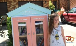 "Maddy Hymas and her little free library stocked with books for young readers who want to ""take a book, leave a book,"" St. George, Utah, June 10, 2016 