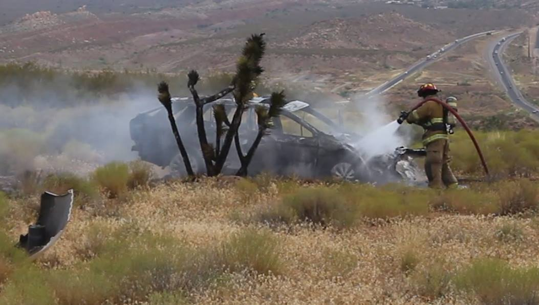 After being forced off the roadway by another vehicle, a Subaru Outback rolled before bursting into flames and igniting a brush fire in the median of Interstate 15 near milepost 19, Washington County, Utah, July 18, 2016 | Photo by Mike Cole, St. George News