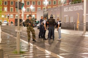 Police officers and a soldier stand by the sealed off area of an attack after a truck drove on the sidewalk and plowed through a crowd of revelers that gathered to watch fireworks in the French resort city of Nice, southern France, Friday, July 15, 2016. | AP Photo/Ciaran Fahey, St. George News)
