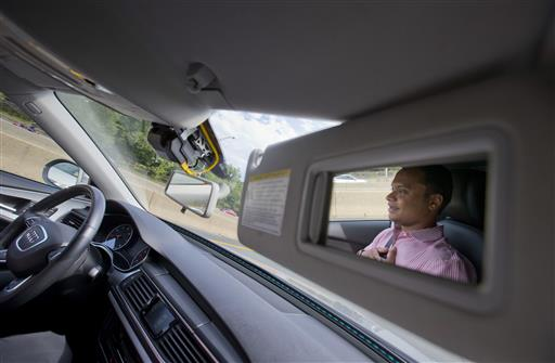 Kaushik Raghu, senior staff engineer at Audi, is reflected in the passenger side visor mirror while demonstrating an Audi self-driving vehicle on I-395 expressway in Arlington, Virginia, Friday, July 15, 2016 | Associated Press photo by Pablo Martinez Monsivais, St. George News