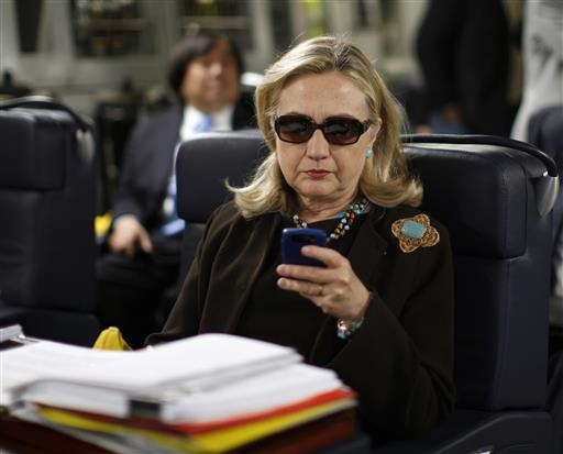 FILE - In this Oct. 18, 2011, file photo, then-Secretary of State Hillary Rodham Clinton checks her Blackberry from a desk inside a C-17 military plane upon her departure from Malta, in the Mediterranean Sea, bound for Tripoli, Libya. The State Department is under fire in courtrooms over its delays turning over government files related to Hillary Clinton's tenure as secretary of state. In one case, the department warned it needed a 27-month delay, until October 2018, to turn over emails from Clinton's former aides. | AP Photo/Kevin Lamarque, Pool, File; St. George News