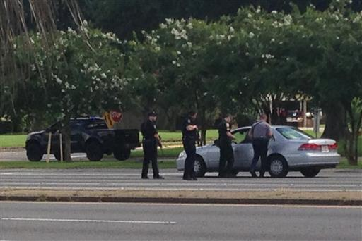 Authorities talk to the driver of a car near an area where several officers were shot while on duty less than a mile from police headquarters, Sunday, July 17, 2016, in Baton Rouge, La.   AP Photo by Mike Kunzelman, St. George News