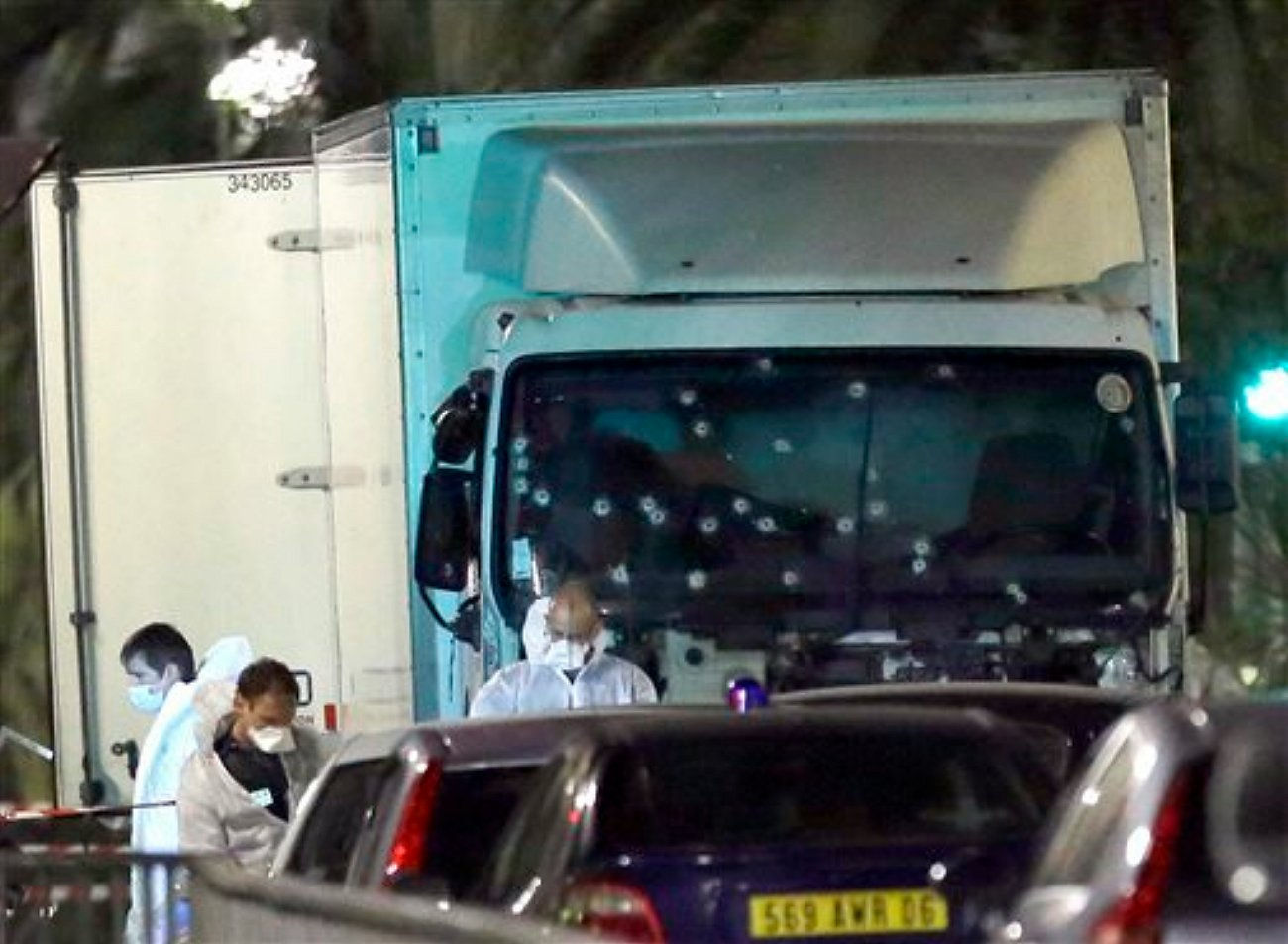 Forensic officers stands near a truck with its windscreen riddled with bullets, that plowed through a crowd of revelers who'd gathered to watch the fireworks in the French resort city of Nice, southern France, Friday, July 15, 2016. At least 80 people were killed before police killed the driver, authorities said, Nice France, July 15, 2016 | AP Photo by Claude Paris, St. George News