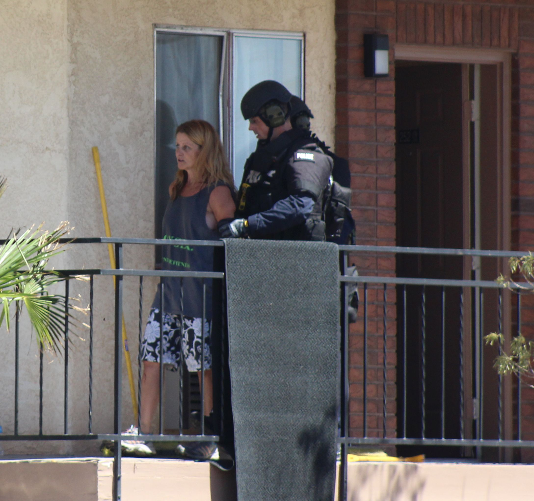 A SWAT team member escorts Melissa Rowan, 46, from her room at the Sun Time Inn where she had been destroying the property. St. George, Utah, July 17, 2016 | Photo by Ric Wayman, St. George News