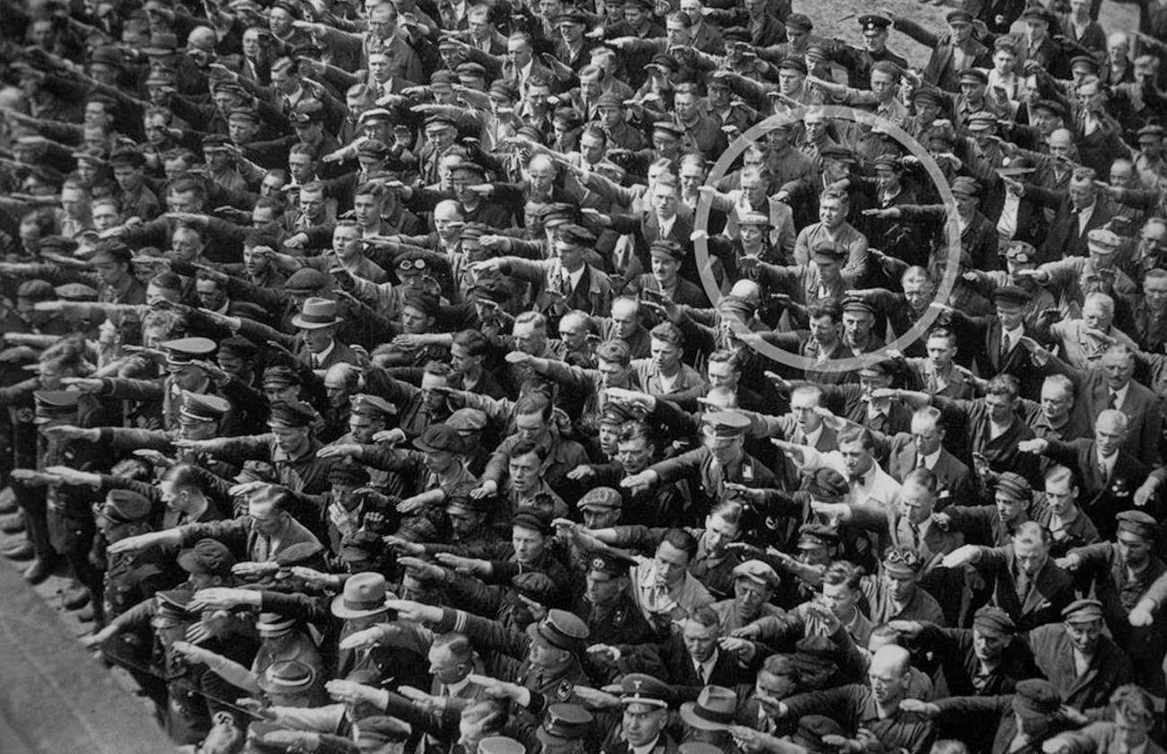 "A lone man refusing to do the ""Sieg Heil"" salute at the launching of the Horst Wessel in Nazi Germany, 1936. 