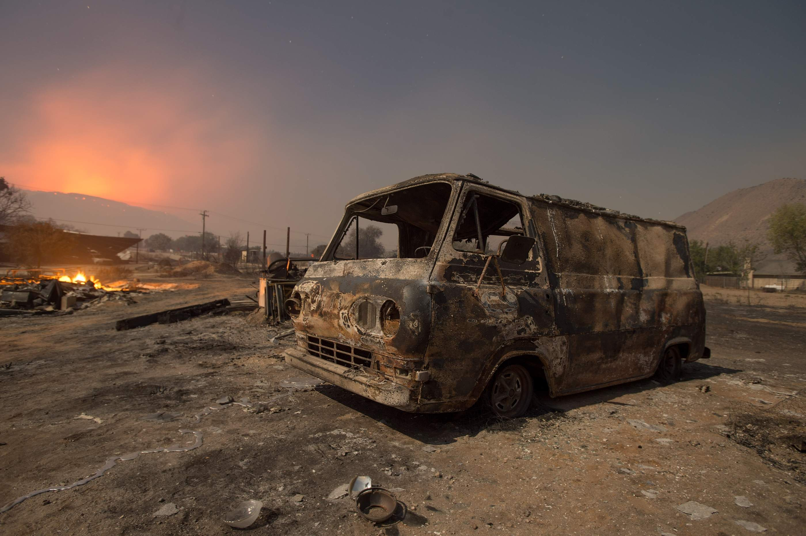Seen in a long exposure nighttime photograph, a burned van rests in a lot while a wildfire glows on the horizon in Phelan, Calif., early Thursday, Aug. 18, 2016 2016. | AP Photo/Noah Berger; St. George News