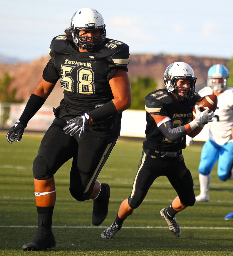 Desert Hills' Penei Sewell (58) leads the way for Brock Perry (21), Desert Hills vs. Salem Hills, Football, St. George, Utah, Aug. 26, 2016, | Photo by Robert Hoppie, ASPpix.com, St. George News