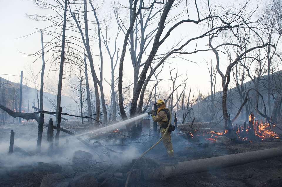 A Cal Fire firefighter sprays a hot spot along Cajon Blvd. off the 15 Freeway after a wildfire burned through the area Wednesday, Aug. 17, 2016, in Keenbrook, Calif. Firefighters had at least established a foothold of control of the blaze the day after it broke out for unknown reasons in the Cajon Pass near Interstate 15, the vital artery between Los Angeles and Las Vegas. | Photo by Kevin Sullivan/The Orange County Register via AP; St. George News