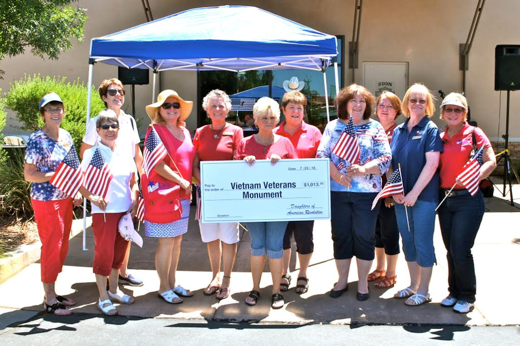 Members of the Daughters of the American Revolution Color Country Chapter present a check to Judith Cooley (center holding the check) and the Vietnam Veterans Monument at a fundraiser for the monument held at Zion Harley Davidson, Washington City, Utah, July 23, 2016 | Photo courtesy of Valerie King, St. George News