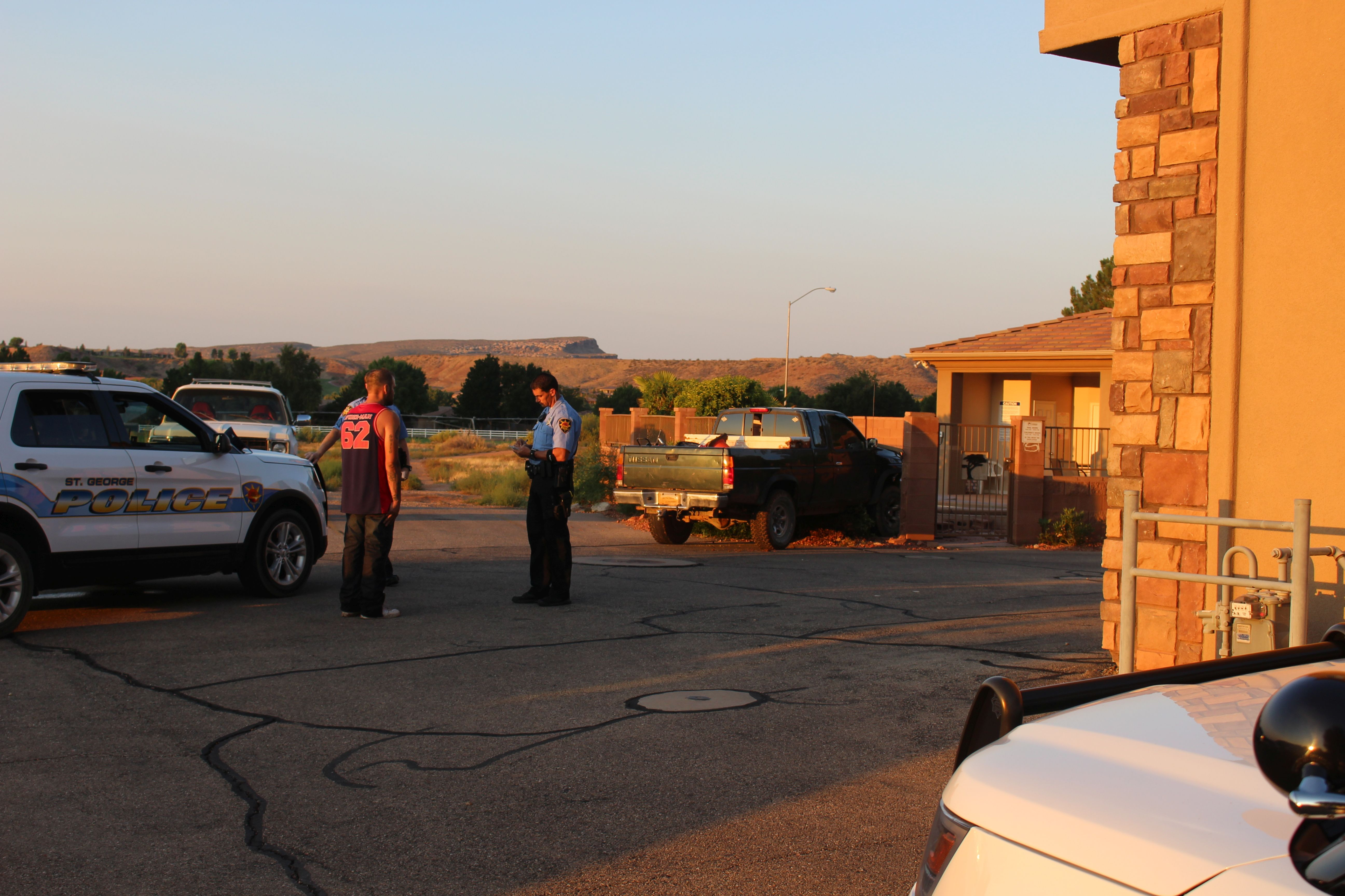 The man who allegedly drove his truck into a brick wall surrounding a swimming pool is given a field sobriety test by St. George Police officers Saturday morning. St. George, Utah, Aug. 20, 2016 | Photo by Ric Wayman, St. George News