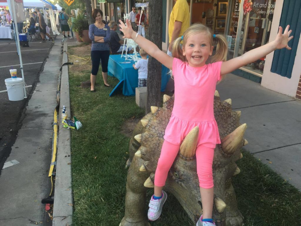 Olivia, 3, poses on a dinosaur sculpture from the St. George Children's Museum while attending George Streetfest, St. George, Utah, August 5, 2016 | Photo by Hollie Reina, St. George News
