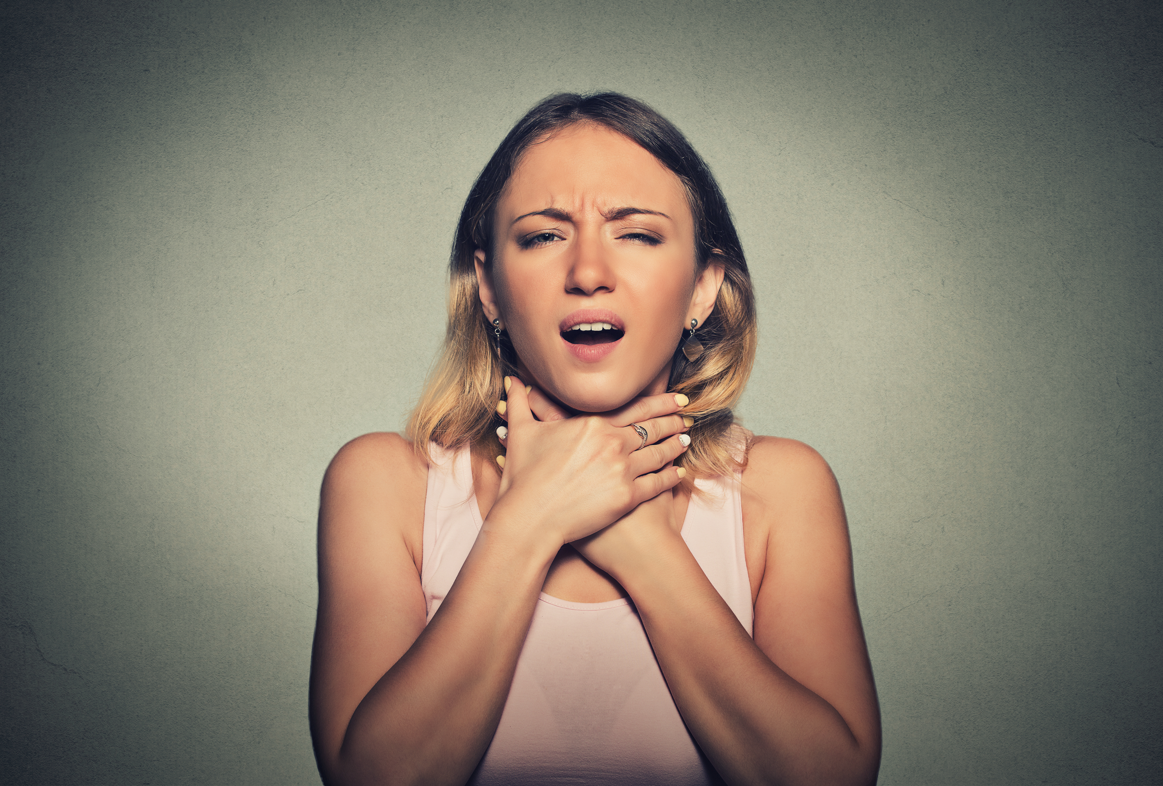 "This photo illustrates a young woman unable to breathe. According to the Mayo Clinic, one of the symptoms of anaphylaxis is constriction of the airways and a swollen tongue or throat, which can cause wheezing and trouble breathing. Its webapge states: ""Anaphylaxis symptoms usually occur within minutes of exposure to an allergen. Sometimes, however, anaphylaxis can occur a half-hour or longer after exposure. Anaphylaxis symptoms include: • Skin reactions, including hives along with itching, and flushed or pale skin (almost always present with anaphylaxis). • A feeling of warmth. • The sensation of a lump in your throat. • Constriction of airways (see above). • A weak and rapid pulse • Nausea, vomiting or diarrhea. • Dizziness or fainting."" Mayo advises emergency medical help be sought immediately. ""If the person having the attack carries an epinephrine autoinjector (such as an EpiPen or EpiPen Jr),"" it advises, ""give him or her a shot right away. Even if symptoms improve after an emergency epinephrine injection, a visit to the emergency department is still necessary to make sure symptoms don't return."" 