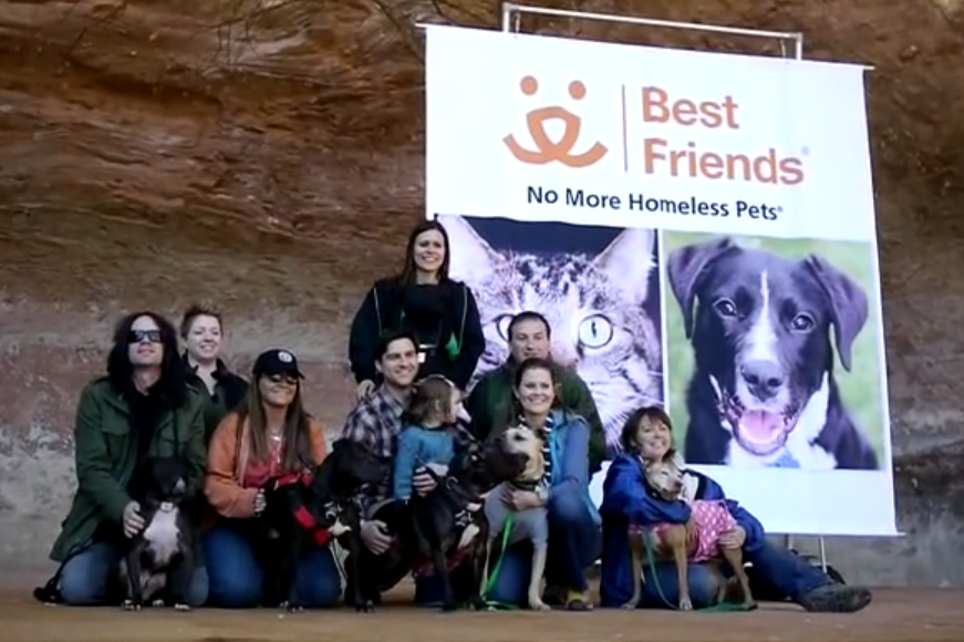 """This 2013 file photo shows six adoptive families and their """"Vicktory dogs,"""" so-named for rescue from the Michael Vick dogfighting organization indicted in 2007, at a reunion at Best Friends Animal Society's Angel's Landing. The event offered a media display of recovery, rehabilitation and hope. Kanab, Utah, March 11, 2013 
