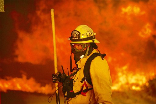 A firefighter prepares to battle a wildfire in the Cajon Pass in San Bernardino county, Calif., on Tuesday. The wildfire that began as a small midmorning patch of flame next to Interstate 15 in the Cajon Pass had by Wednesday afternoon turned into a 47-square-mile monster that burned an untold number of homes. San Bernardino County, California, Aug. 16, 2016   Photo by Stan Lim /The Press-Enterprise via AP, St. George News