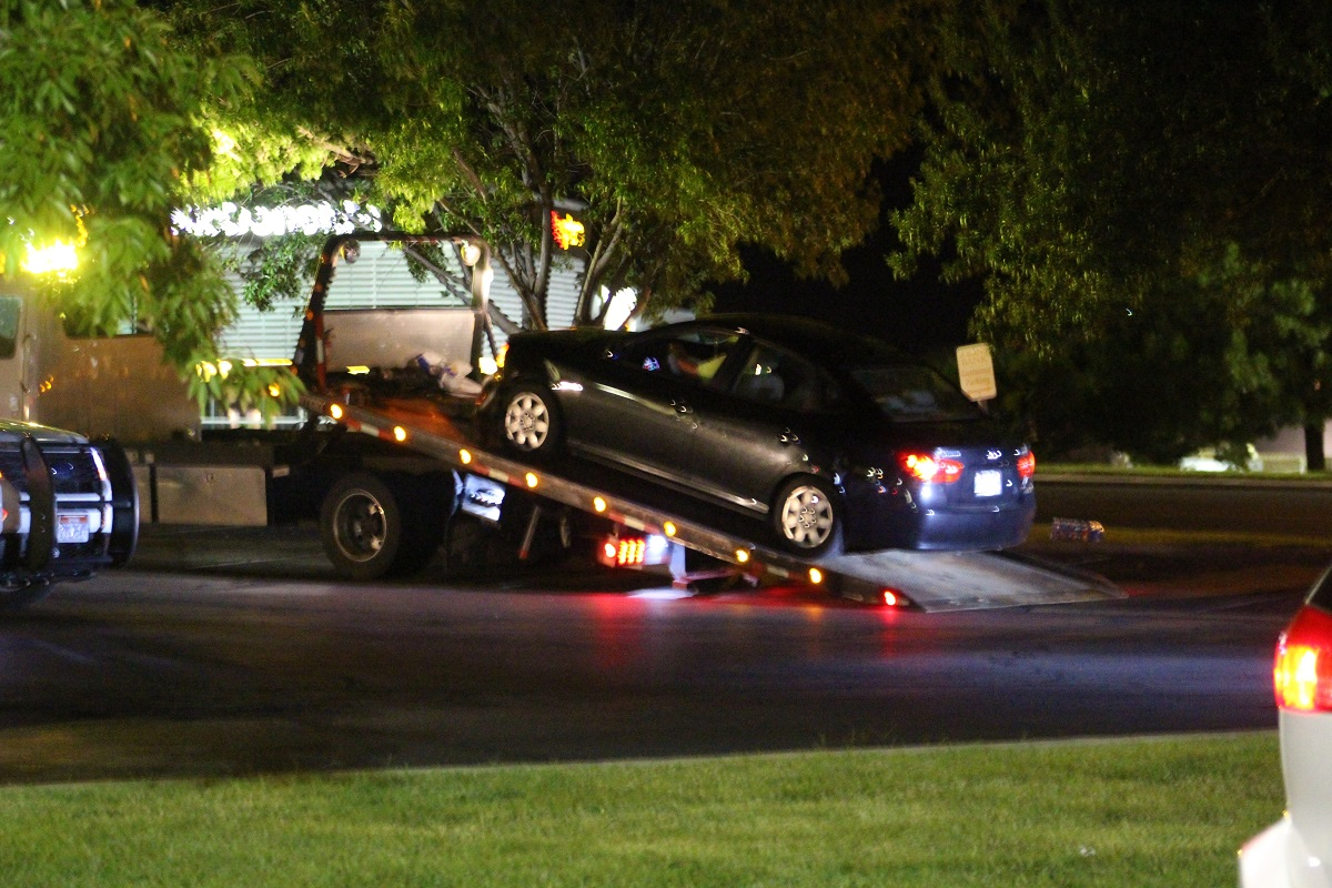 Black four-door sedan is towed after two-car collision in the intersection of Sunset Boulevard and Dixie Downs Road, St. George, Utah, Aug. 28, 2016 | Photo by Cody Blowers, St. George News