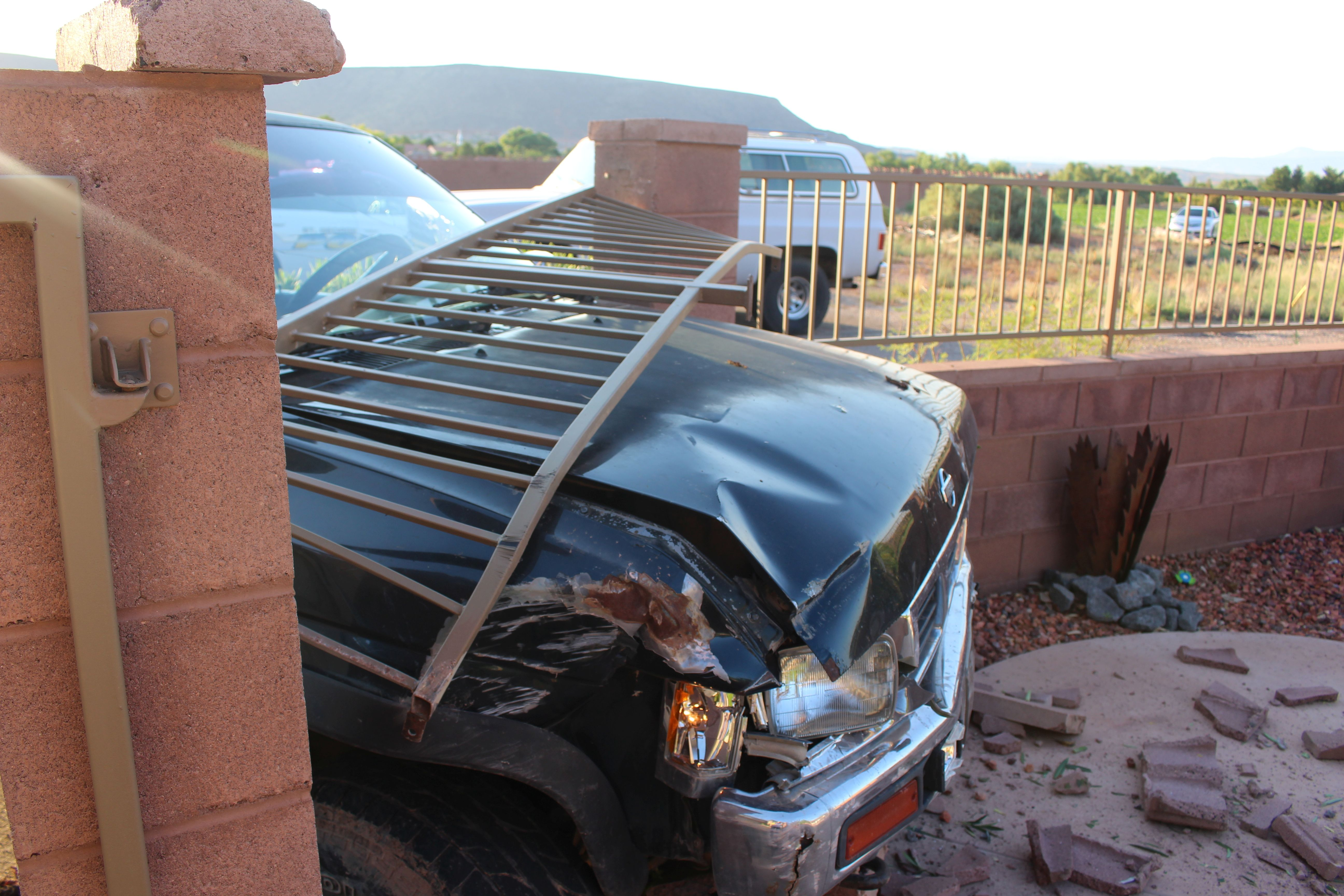 A compact pickup truck crashed into a fence surrounding a swimming pool Saturday. The driver was arrested for DUI, among other things. St. George, Utah, Aug. 20, 2016 | Photo by Ric Wayman, St. George News