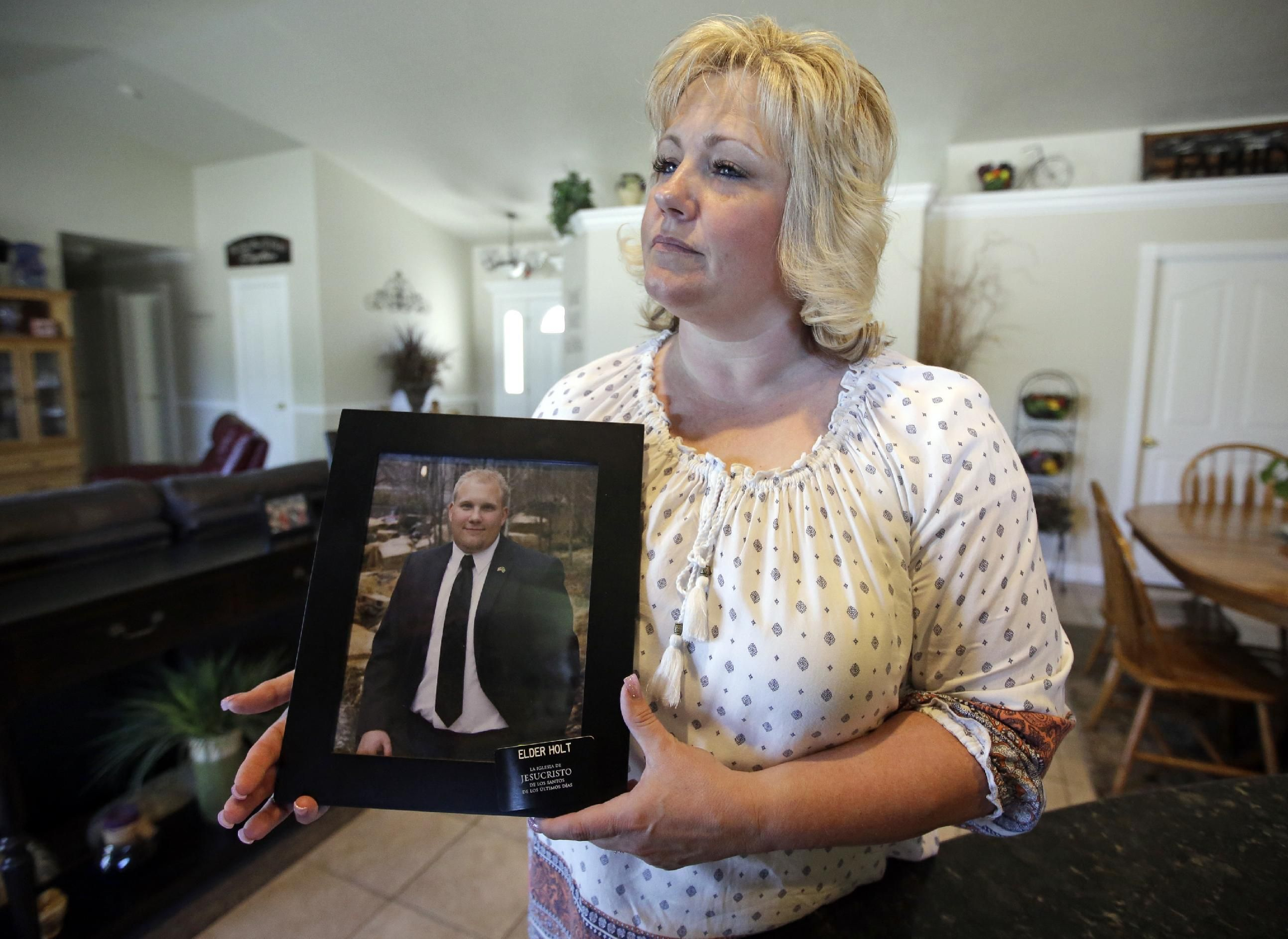 In this July 13, 2016 file photo, Laurie Holt holds a photograph of her son Josh Holt at her home, in Riverton, Utah. U.S. congresswoman Mia Love said Wednesday, Aug. 31 she will call on the State Department to do more to free Josh Holt, a Utah man who's been jailed in Venezuela for two months on weapons charges. | AP File Photo/Rick Bowmer, St. George News