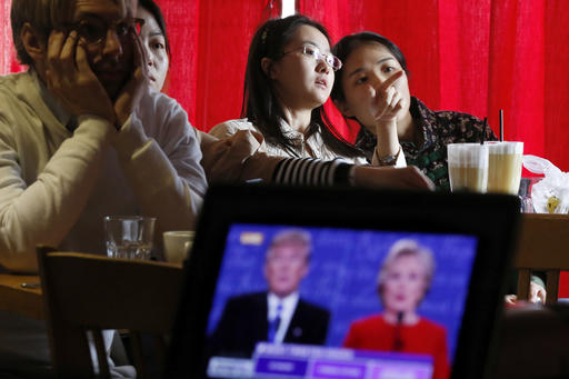 Chinese students chat as they watch a live broadcasting of the presidential debate between Democratic presidential nominee Hillary Clinton and Republican presidential nominee Donald Trump, at a cafe in Beijing, Tuesday, Sept. 27, 2016. (AP Photo/Andy Wong)