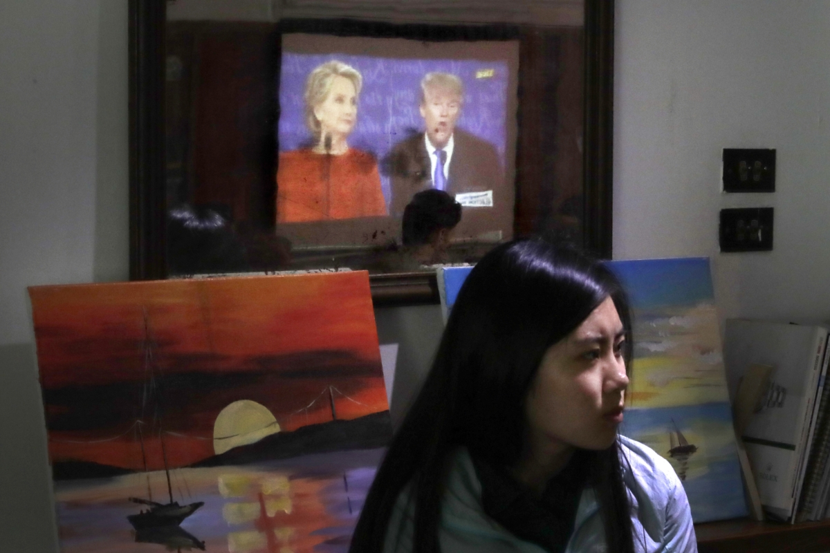 A Chinese woman watches a live broadcasting of the U.S. presidential debate between Democratic presidential nominee Hillary Clinton and Republican presidential nominee Donald Trump reflected on a mirror at a cafe in Beijing, Tuesday, Sept. 27, 2016   AP Photo/Andy Wong, St. George News