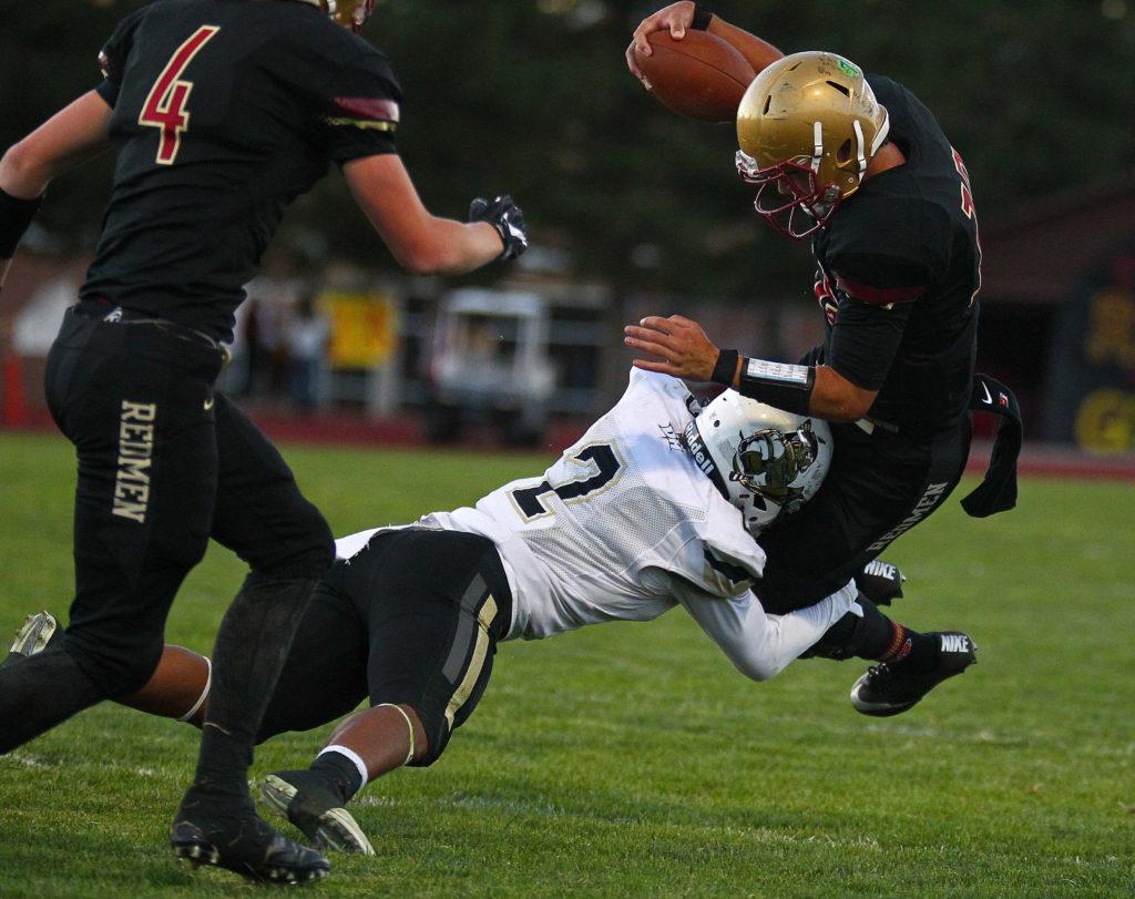 Desert Hills' Nephi Sewell (2) makes a tackle on Cedar's Mason Fakahua (12), Cedar vs. Desert Hills, Football, Cedar City, Utah, Sept. 16, 2016, | Photo by Robert Hoppie, ASPpix.com, St. George News