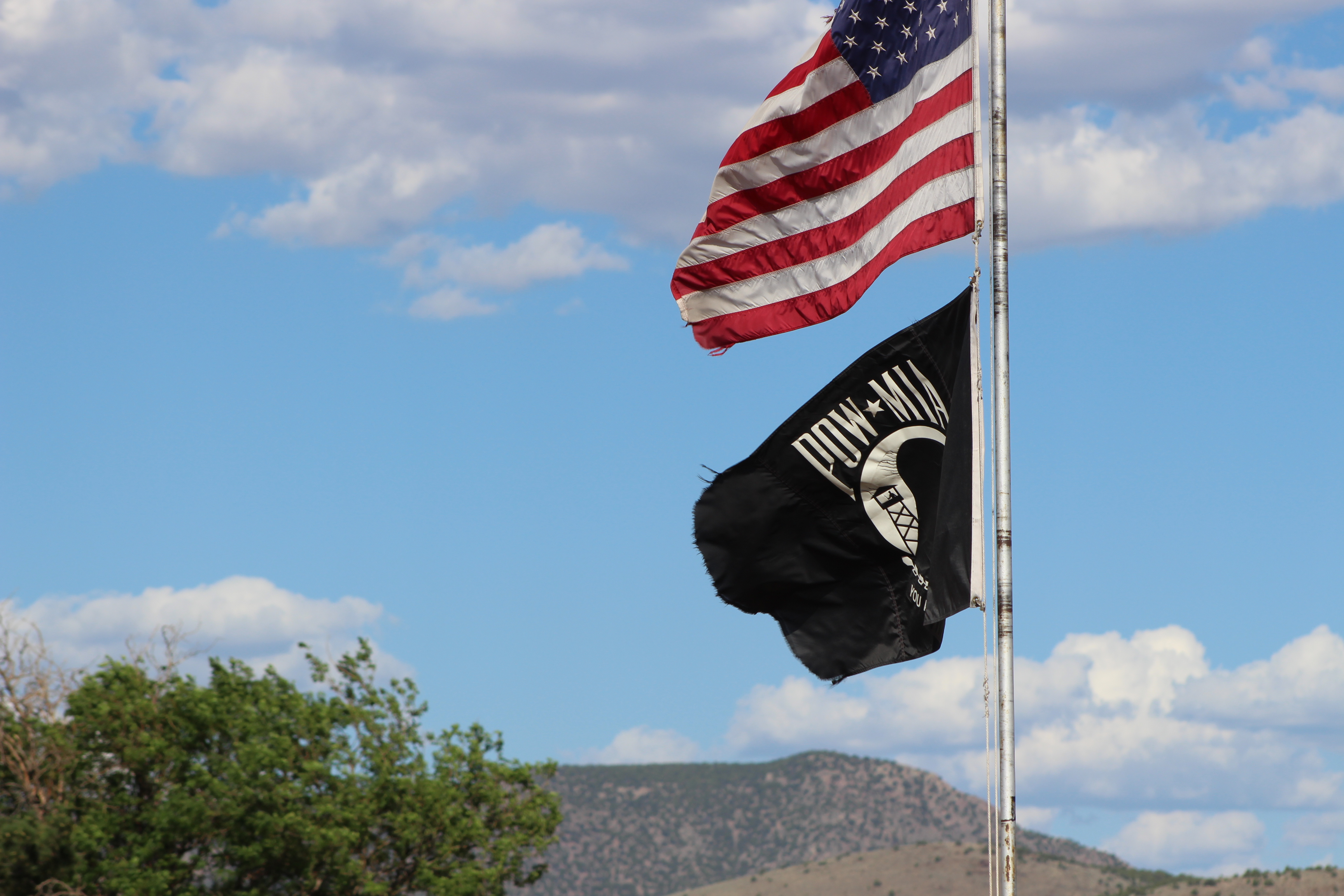 Old Glory, shown here above a POW-MIA flag, still waves proudly in a tiny spot in America where Deputy Jobe Peterson patrols. The people there hold tight to their God, guns and traditional ways of life. Iron County, Utah, July 15, 2016 | Photo by Tracie Sullivan, St. George News / Cedar City News