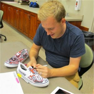 Jacob Amundsen decorates shoes at 2013 Day of the Walking Dead, Location not given | Photo courtesy of Southern Utah University, St. George News, Cedar City News
