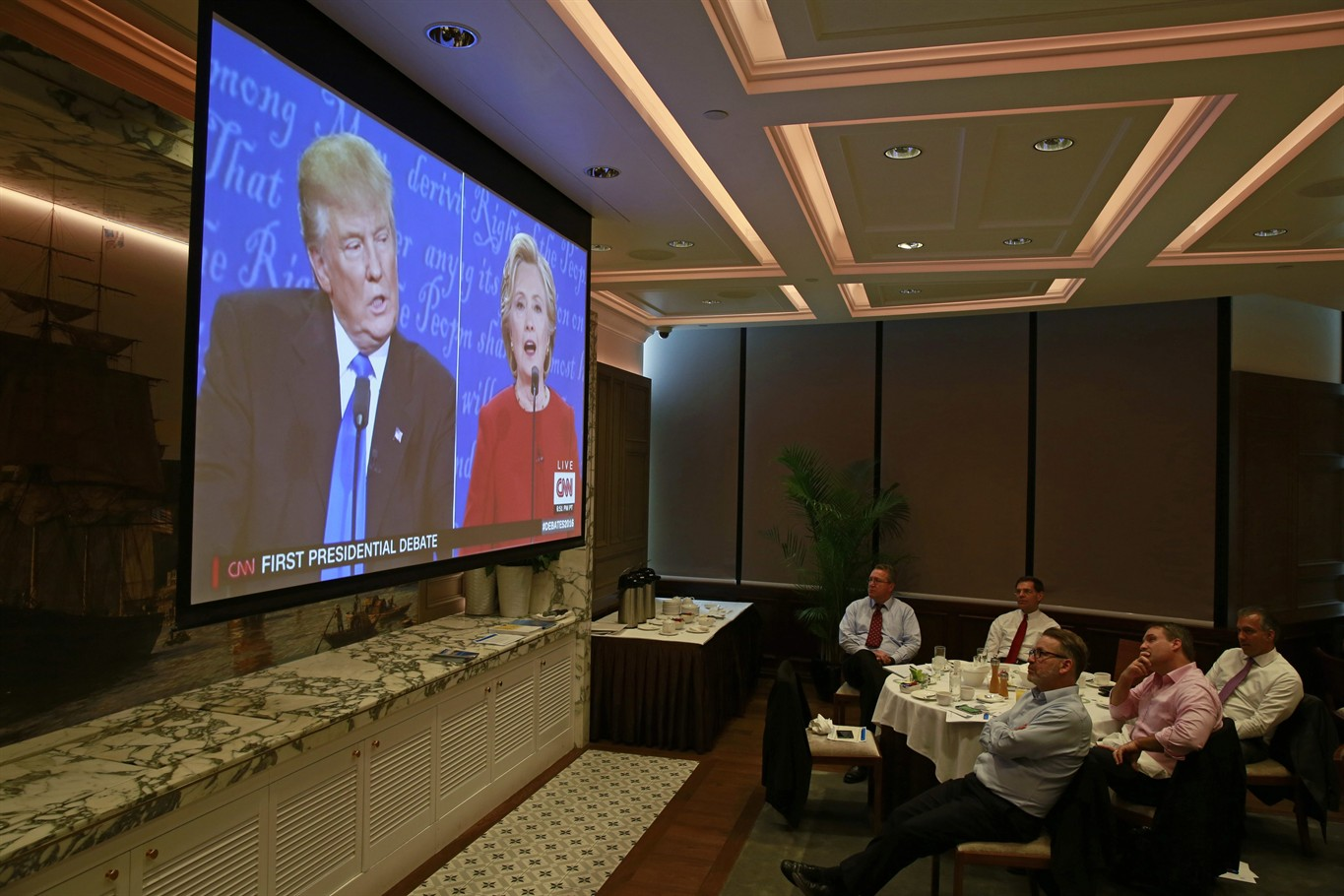 People watch live broadcasting of the U.S. presidential debate between Democratic presidential nominee Hillary Clinton and Republican presidential nominee Donald Trump, at the American Club Hong Kong, Tuesday, Sept. 27, 2016   AP Photo/Kin Cheung, St. George News