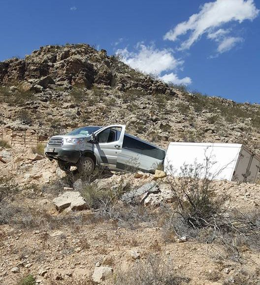 A van forced off I-15 in Arizona hangs over the edge of a precipice about 50 feet above the roadway Tuesday. Mohave County, Arizona, Sept. 13, 2016 | Photo courtesy of Arizona Highway Patrol Trooper Tom Callister, St. George News