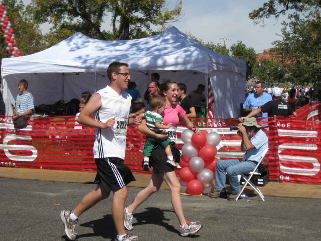 L-R Austin Cope and Laura Cope finish the 2009 St. George Marathon with their young child in arms, St. George Utah, circa October 2009 | Photo courtesy of Laura Cope, St. George News
