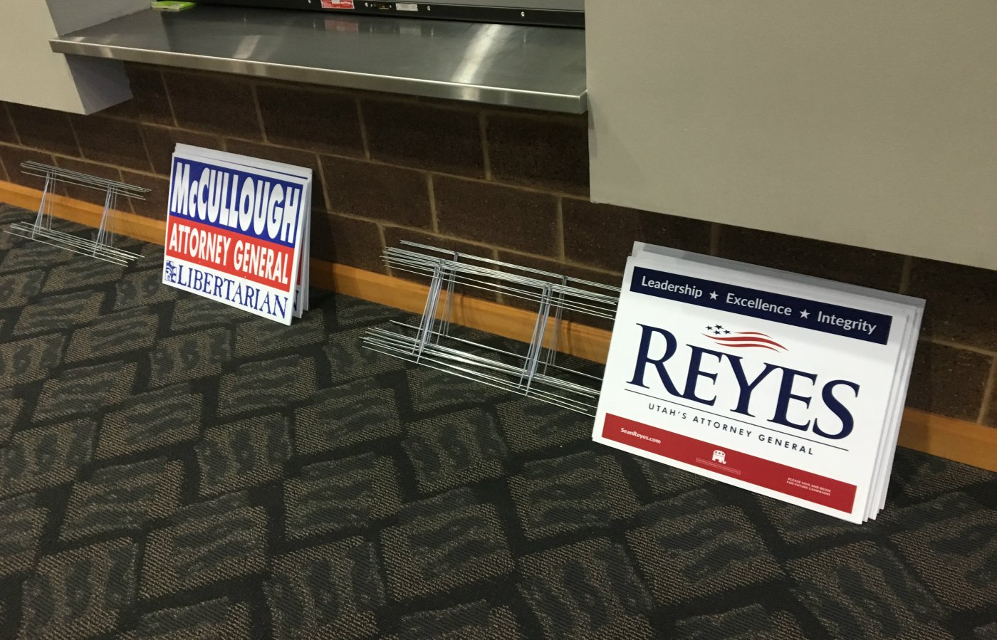 """Campaign signs for Utah Attorney Libertarian candidate Andrew McCullough and Republican incumbent Sean Reyes set against the wall while the """"modified"""" Utah Attorney General dabate takes place, St. George, Utah, Sept. 21, 2016 